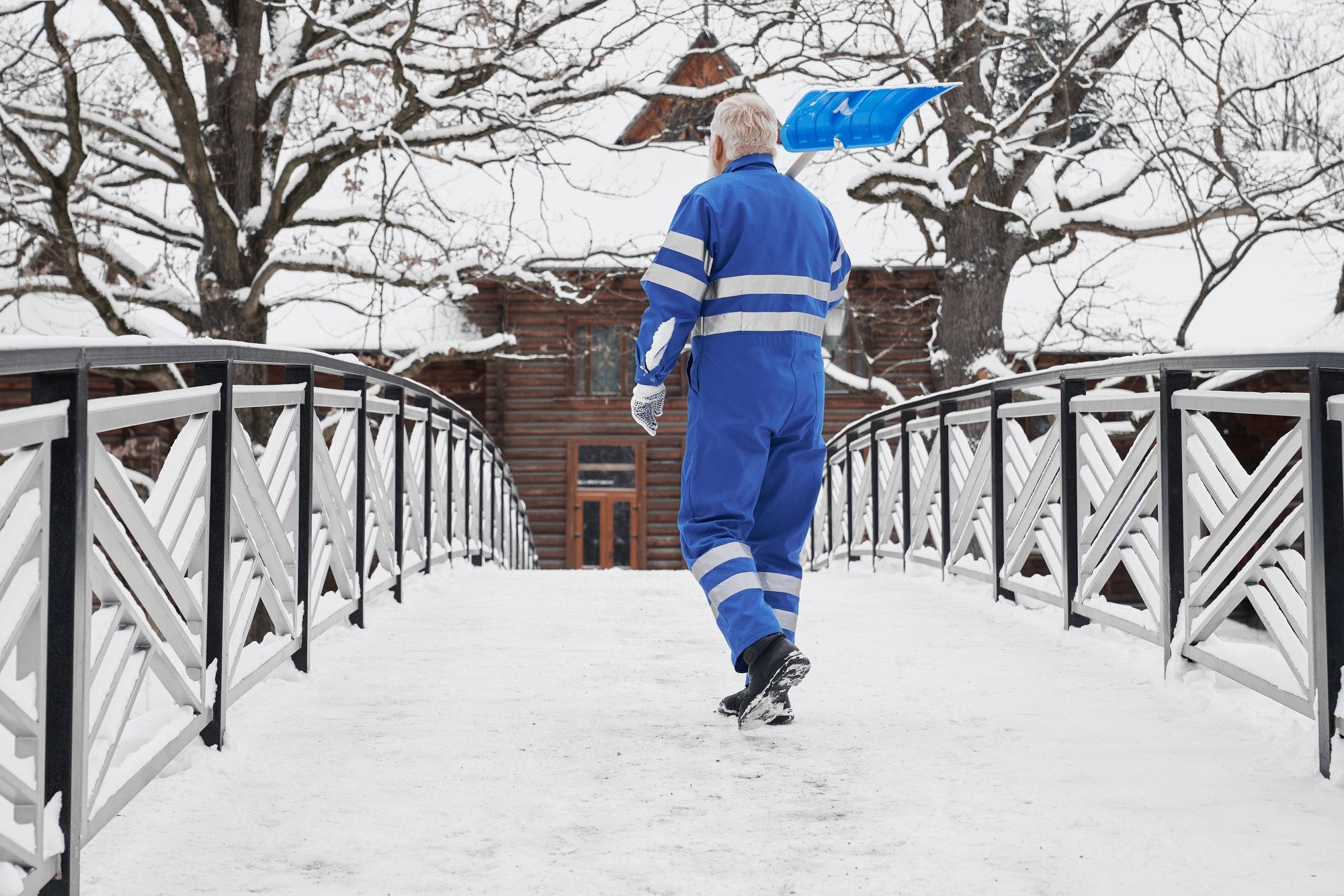 Man with snow shovel on shoulder back view