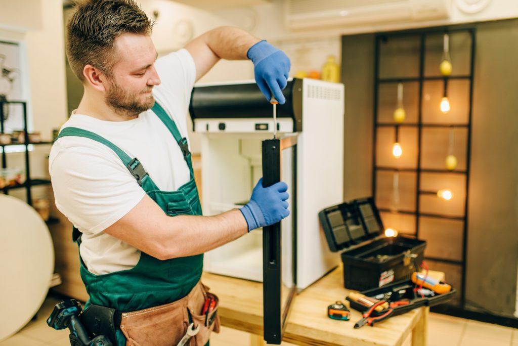 Worker with screwdriver repairs refrigerator door